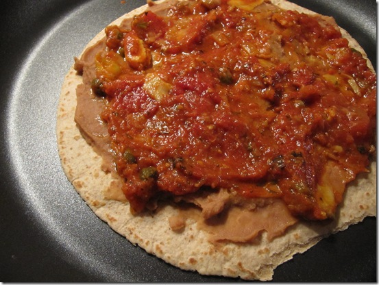 Sauce on top of refried beans on top of tortilla on top of pan
